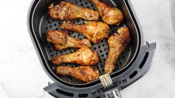 air fried chicken drumsticks in air fryer basket.