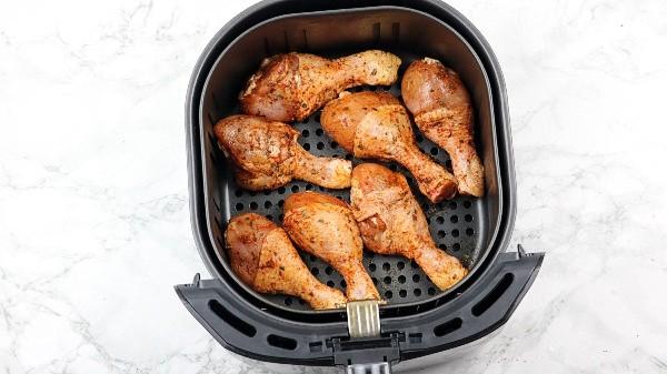 chicken drumsticks in air fryer basket.