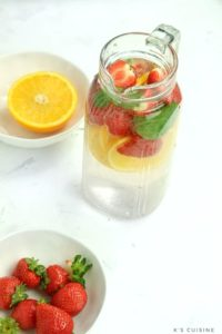 strawberries and orange slices with infused water on display.