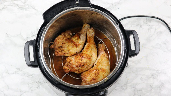Browned chicken arranged on trivet in the instant pot.