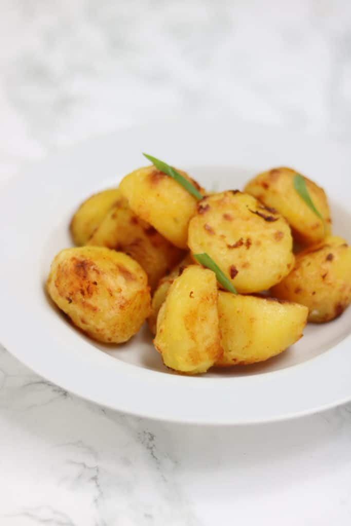 crispy roasted potatoes served in a white plate.