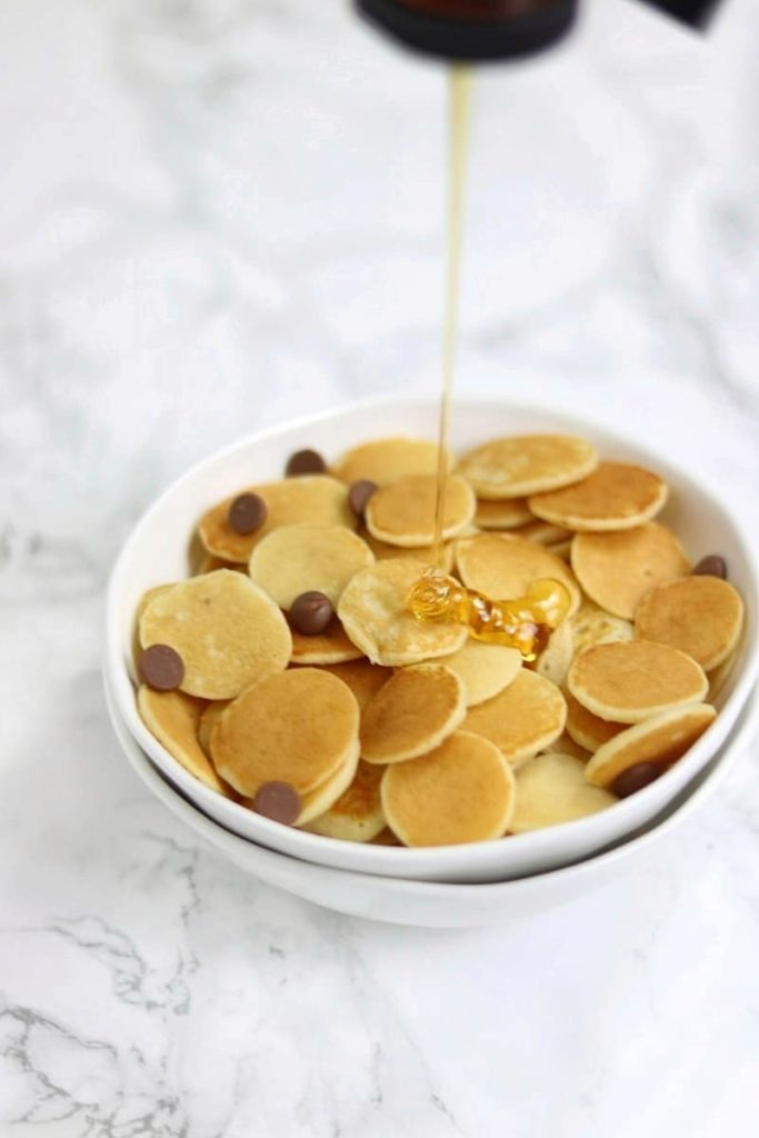 mini pancakes in a white bowl with syrup drip.