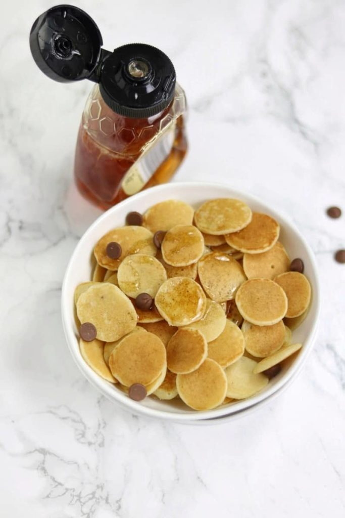 mini pancakes with syrup on the side of the plate.