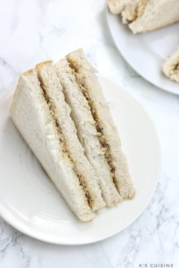 Sardine sandwiches served on a cream flat plate.