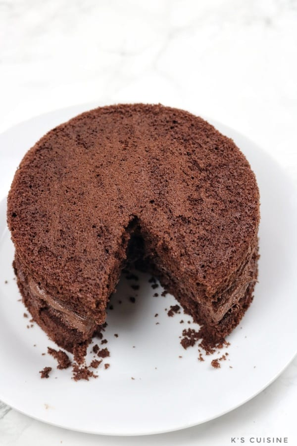 round chocolate cake on a white plate with a portion cut out.